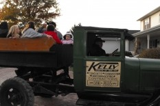 image of older pickup truck with Kelly Designs logo on door and friends sitting in the back