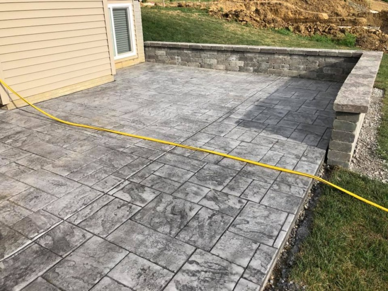 ashlar cut stamped patio with retaining wall