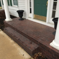 Brick Stamped Porch With White Pillars