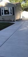 Side Concrete Driveway To A Tan Home