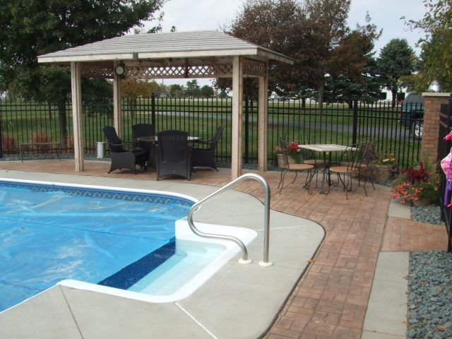 Concrete walkway alongside a pool in a backyard, walkway designed and created by Kelly Designs in Concrete