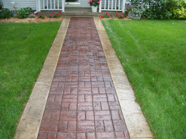 Brick and concrete walkway leading to a house